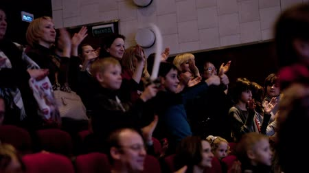 premiere : MOSCOW, RUSSIA - DECEMBER 16, 2013: Impressed spectators applauding after Treasure Island musical in Aquamarine theatre. Sequence of two shots