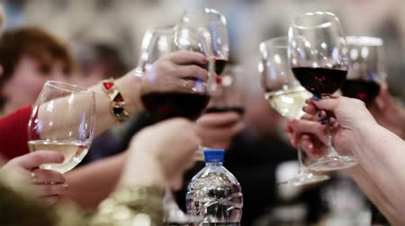 to celebrate : People clanging glasses with white and red wine during celebration. Parties and banquets