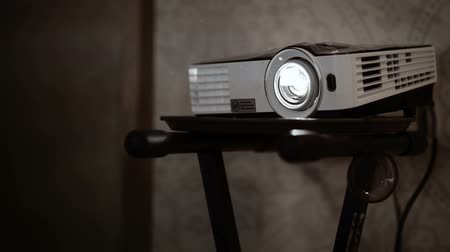 projetor : Digital multimedia projector standing on the rack in work. Bright light in the beginning, darker at the end