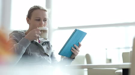 кофе : Young woman using her touchpad while drinking coffee in cafe