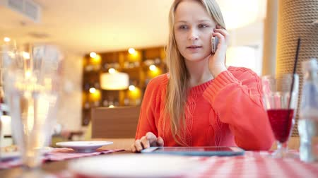 ресторан : Young woman in cafe using her touchpad and then answering phone call