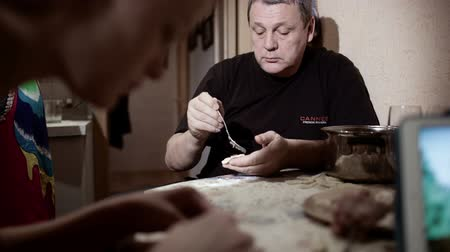 vareniki : Family making pelmeni: one person giving dough, other man and woman stuffing them and talking