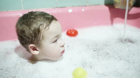 купаться : Little boy sitting in the water with foam during his evening bathing. Water pouring and toys floating around