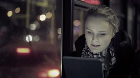 ônibus : Young woman watching video on touchpad during evening ride in the bus. Defocused city traffic in the bus window