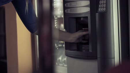 vending machine : Woman taking a plastic cup from coffee vending machine and pushing some buttons