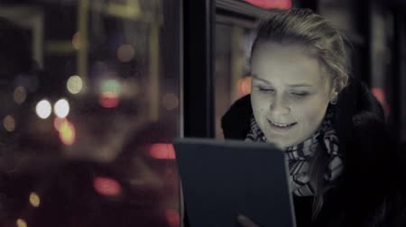 устройство : Young woman watching video on touchpad, then choosing another one during evening ride in the bus. Defocused city traffic in the bus window Стоковые видеозаписи