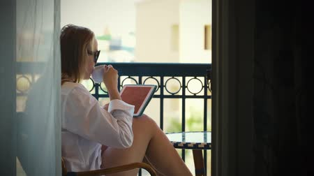 portátil : Dolly shot of young woman using tablet PC and having tea on hotel balcony Vídeos