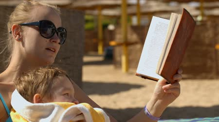 points of interest : Panning shot of mother reading book to her son on the beach. Boy pointing at pictures in the book Stock Footage