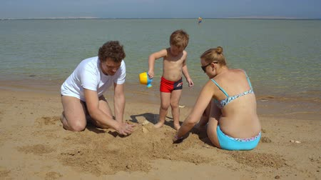 épít : Happy family of three on the beach. Mother and father making sand castle, their son bringing water