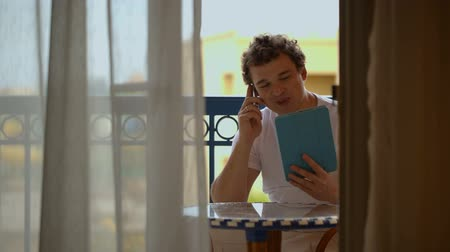 erkély : Young man talking on the phone with tablet PC in hands on hotel balcony