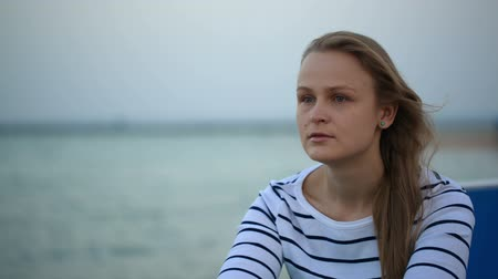 wistful : Young thoughtful woman sitting by the sea and looking into the distance Stock Footage