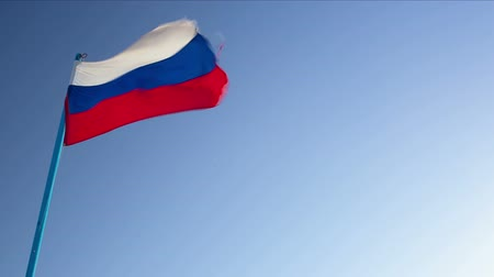 esinti : Dolly shot of Russian and German flags waving in the breeze against clear blue sky