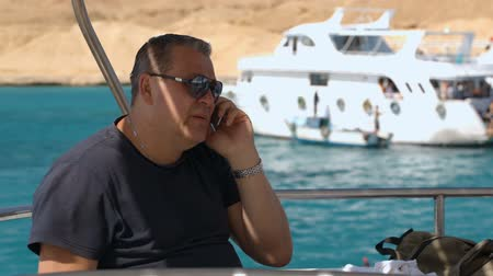 falar : Mature man talking on the phone being on the yacht. Blue sea and yacht with passengers in the background Vídeos