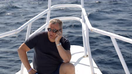 falar : 50 years old man sitting on the bow of sailing yacht and talking on the phone Vídeos