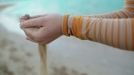 pour out : Dolly shot of female hands filtering the sand. Summer vacation and time metaphor