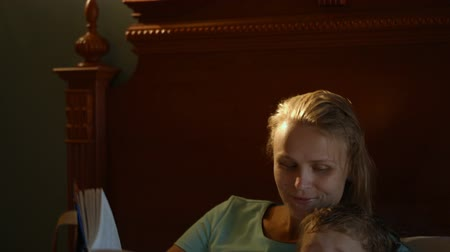 points of interest : Tlit shot of mother and son lying in bed. Mom reading a book aloud while her son watching TV