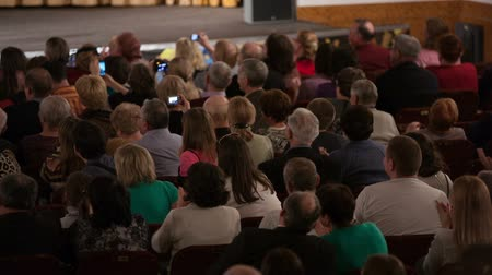 stage theater : Grateful audience applauding and taking pictures. View from the back of a packed auditorium or theatre with people seated in an audience watching a live performance on a stage