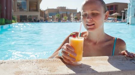 meyve suyu : Dolly shot of young woman relaxing in the pool having fruit cocktail and enjoying wonderful day Stok Video