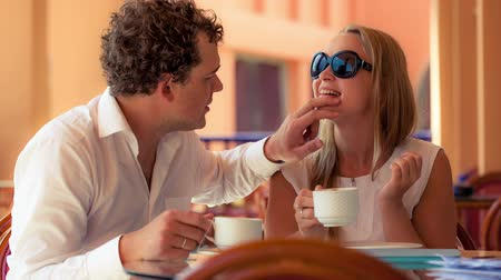 herbata : Lovely couple in a cafe having tea. Man cleaning womans face while she making funny grimace