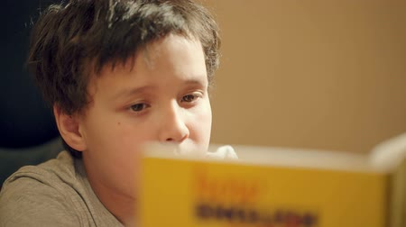 öykü : Dolly shot of young boy concentrating on reading a book with just his eyes visible over the top as he studies for class