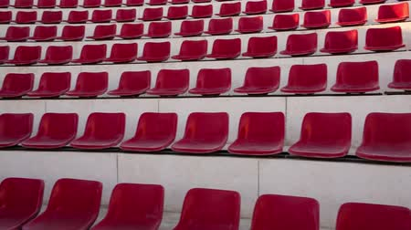 арена : Tilt shot of empty red seats at the stadium or outdoor stage