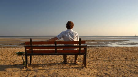 bank : Young man sitting alone on the bench on the beach