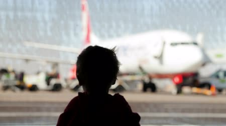 Little boy watching planes at the airport standing in silhouette with his back to the camera at a large window overlooking the tarmac 影像素材