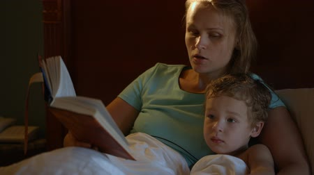 öykü : Tilt shot of mother and son in bed at night. Mom reading aloud before bed, boy watching TV
