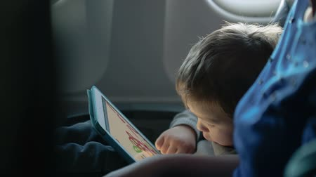 таблетка : Little boy traveling in an airplane sitting in his seat playing with a tablet computer watched by a parent Стоковые видеозаписи