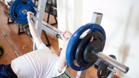 musculação : Mature man working out lifting the weight bar in the gym