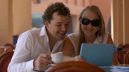 ebéd : Man and woman watching photos on tablet pc having tea and kissing Stock mozgókép