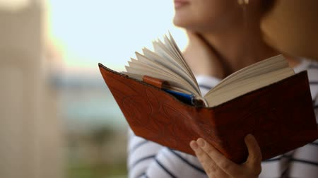 pensamento : Tilt shot of a woman being deep in thoughts or dreams, while the wind stirring the pages of the book in her hands Stock Footage