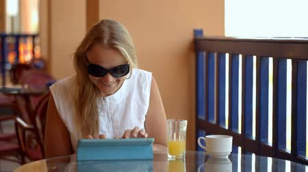 eszköz : Dolly shot of young woman on cafe terrace using laptop, drinking fresh juice and enjoying outside view
