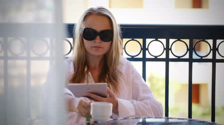 Dolly shot of attractive young woman in sunglasses sitting reading a tablet -pc on a balcony as she sits enjoying a cup of coffee or tea, view from inside the house looking out
