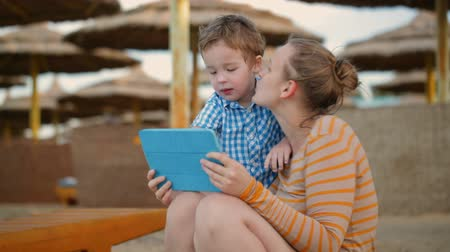 tabletler : Little boy with his mother at a beach resort playing with a tablet computer on the beach under straw beach umbrellas Stok Video