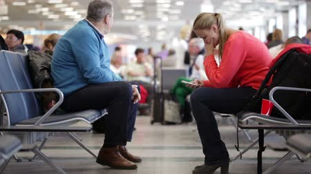 sitting room : Father and daughter waiting for their flight in the lounge. Daughter using phone and father sitting quietly Stock Footage
