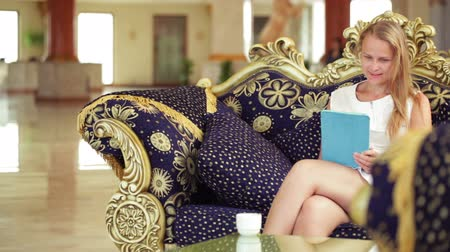 мебель : Beautiful woman using a tablet in a hotel lobby sitting enjoying a cup of coffee on an ornate couch smiling as she reads the screen Стоковые видеозаписи