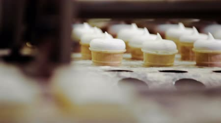 ipari : Close-up shot of automatic machine moving ready ice-cream cones to the running conveyer. Focus changing from background to foreground