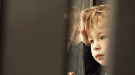lonely : Little boy looking out of the window with his face and hands close to it and reflected in the glass Stock Footage