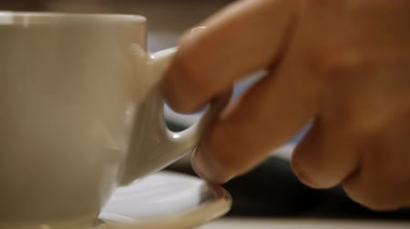 sadece kadınlar : Close-up shot of a woman having a cup of coffee during using tablet PC. Only hand, cup and pad in shot. Focus on the cup of coffee