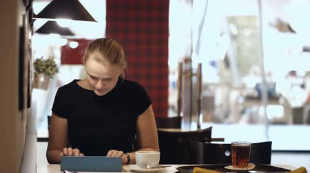 xícara de café : Young woman sitting alone in cafe and typing on her tablet while drinking coffee