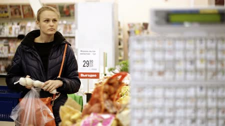 супермаркет : Young woman shopping in supermarket and choosing fresh  vegetables, digital scales in foreground. Shot with changing focus Стоковые видеозаписи