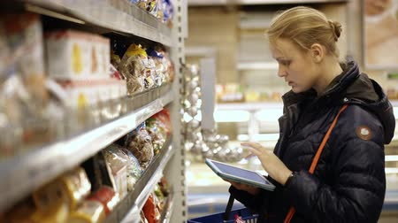 супермаркет : Young woman buying products in grocery checking them with the shopping list on touchpad