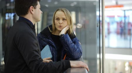 bizonyítani : Young man and woman discussing something in shopping center. Woman trying to explain her point of view with gestures