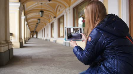 tiro : Young woman with touchpad hunkering down to make a shot of classic style hall in perspective, then she going away Stock Footage