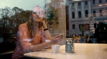 olhares : Young woman in cafe using phone and looking out the window with thoughful look. City life reflecting in the glass Vídeos