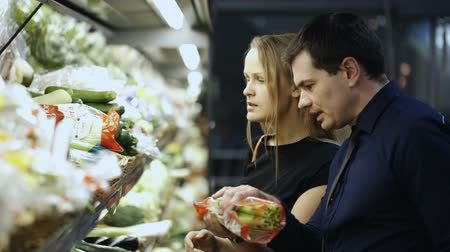 grocery : Young man and woman in grocery choosing fresh vegetables, checking them at first