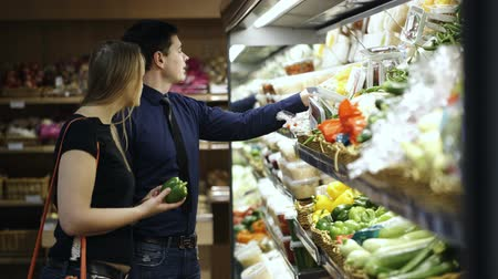 grocery : Young couple choosing fresh vegetables in grocery and putting them in the shopping basket Stock Footage