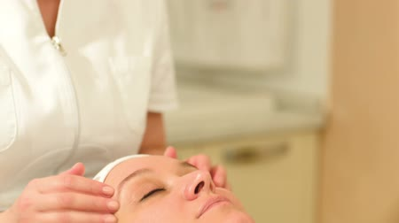 przychodnia : Tilt and dolly shot of woman relaxed under professional facial massage at beauty spa