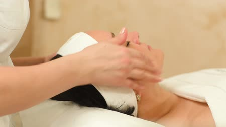 terapeuta : Dolly shot of massage therapist providing a seance of facial massage at beauty spa Stock Footage